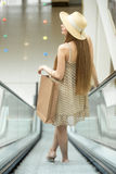 Woman in shopping centre riding on escalator. Back view Royalty Free Stock Image