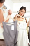Woman shopping choosing dresses. Looking in mirror uncertain. Beautiful young multicultural shopper in clothing store stock image