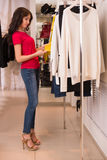 Woman shopping choosing dresses Stock Images