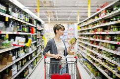 Woman shopping and choosing goods at supermarket. Pretty woman with a cart shopping and choosing goods at the supermarket royalty free stock photo
