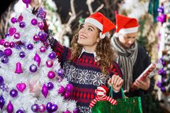 Woman Shopping For Christmas Decorations. Happy young women shopping for Christmas decorations with men in store Royalty Free Stock Photo