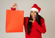 Woman shopping for christmas gifts with shopping bags and santa hat looking excited and happy stock image