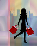 Woman shopping in the city. Beautiful and fashion  shopping girl in front of degraded glasses of color and city background with bags Stock Photos