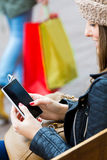 Woman shopping in the city with his smartphone Stock Photos