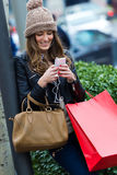 Woman shopping in the city with his smartphone Stock Image
