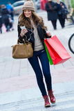 Woman shopping in the city with his smartphone Royalty Free Stock Photos
