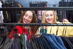 Woman shopping clothes. Beautiful women choosing garments in the clothing store. Female friends having fun shopping in the boutique Royalty Free Stock Photography