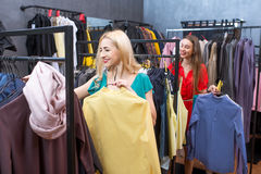 Woman shopping clothes. Beautiful women choosing garments in the clothing store. Female friends having fun shopping in the boutique Royalty Free Stock Photo