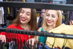 Woman shopping clothes. Beautiful women choosing garments in the clothing store. Female friends having fun shopping in the boutique Stock Images