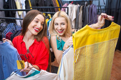 Woman shopping clothes. Beautiful women choosing garments in the clothing store. Female friends having fun shopping in the boutique Stock Photography