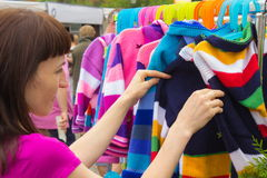 Woman shopping clothes on stall at the bazaar Royalty Free Stock Images