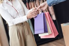 Woman shopping in clothes store. Partial view of woman taking shopping bags from shop assistant while shopping in clothes store Stock Photos