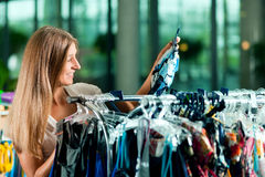 Woman shopping in a clothing store Stock Images