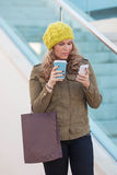 Woman shopping with coffee and phone stock images
