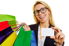 Woman shopping with credit card. Happy woman with many shopping bags holding an empty credit card Stock Image