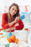 Woman shopping with a credit card. Smiling woman doing grocery shopping at the supermarket she is leaning on a full cart and holding a credit card Royalty Free Stock Photo