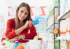 Woman shopping with a credit card. Smiling woman doing grocery shopping at the supermarket she is leaning on a full cart and holding a credit card Royalty Free Stock Photography