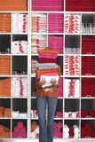 Woman shopping in department store, holding large pile of towels beside shelf, face obscured Stock Photo