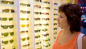 Woman shopping for eyeglasses. A pretty, middle aged woman looking at a large display of eyeglasses or sunglasses in a shop or store Royalty Free Stock Photography