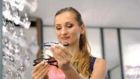 Woman shopping eyeglasses choosing between the models stock video footage