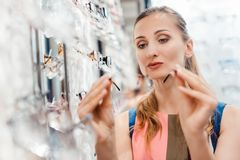 Woman shopping eyeglasses choosing between the models stock photos