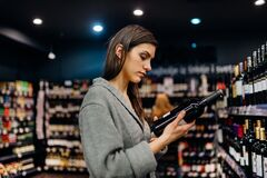 Free Woman Shopping For Expensive Wine In Supermarket Alcohol Store.Choosing And Buying Good Cheap Wine.Benefits Of Drinking Wine. Stock Image - 177523811