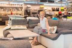 Woman shopping for furniture, sofa and home decor in store. Caucasian woman shopping for furniture, sofa and home decor in store. Lady sitting on couch imagining Stock Images