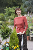 Woman shopping in garden centre, pushing trolley full with pot plants, smiling, portrait Royalty Free Stock Image