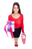 Woman Shopping gifts. Young woman in red with shopping bag and gift Isolated on White Royalty Free Stock Image