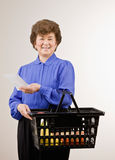 Woman shopping for groceries with shopping list. Confident woman shopping for groceries with shopping list and holding basket Stock Photos