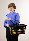 Woman shopping for groceries with shopping list. Confident woman shopping for groceries with shopping list and holding basket Royalty Free Stock Photo