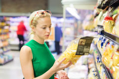 Woman shopping groceries at supermarket. Stock Images