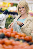 Woman shopping in grocery section of supermarket, putting tomatoes in plastic bag, smiling, portrait Stock Image