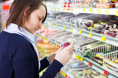 Woman shopping in grocery store stock image