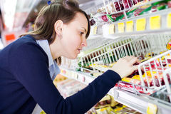 Woman shopping in grocery store. Young woman shopping in a grocery store looking at products royalty free stock images