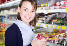 Woman shopping in grocery store. Smiling young woman shopping in a grocery store holding a product stock photography