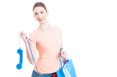 Woman at shopping hanging a telephone receiver and smiling Stock Images