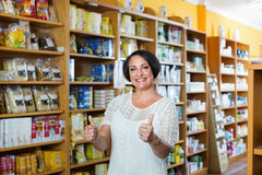 Woman shopping health supplements in drugstore. Happy satisfied mature brunette woman shopping health supplements in drugstore stock photos