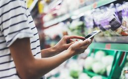 Woman shopping healthy food in supermarket background. Close up view girl buy products using digital gadget in store. Hipster. At grocery using smartphone stock photography