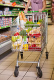 Woman shopping with her trolley full of products Royalty Free Stock Photos