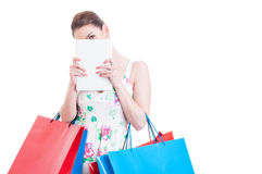 Woman at shopping hiding over a tablet Stock Photos