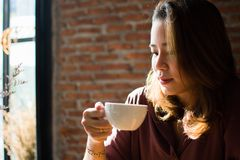 A beautiful woman is looking into the cup of coffee. A beautiful woman is holding and looking into the cup of coffee before drinking it stock photo