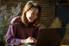 A woman is shopping on the internet while putting the little smile on her face stock image