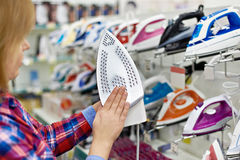 Woman shopping for iron in store Royalty Free Stock Images