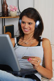 Woman shopping on line. A woman listening to headphones and placing an order on the internet Royalty Free Stock Photography