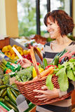 Woman with shopping list buying vegetables. Smiling woman with shopping list buying fresh vegetables in a supermarket Royalty Free Stock Photography