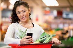Woman with Shopping List on Phone. Smiling young woman using mobile phone while shopping in shopping store and looking at camera Royalty Free Stock Photo