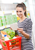 Woman with shopping list. Woman at supermarket holding a full shopping basket and a shopping list royalty free stock images