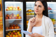 Woman with shopping list. Thoughtful young woman holding shopping list and looking away while standing in front of refrigerators in grocery store Royalty Free Stock Photography