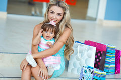 Woman during the shopping with the little girl. Happy family,Mother and her little daughter,go shopping with colored bags together when shopping,family shopping Royalty Free Stock Images